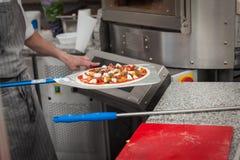 Koch zieht lave gebackene Pizza Stockbild