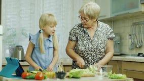 Koch zusammen Das Mädchen von 6 Jahren hilft ihrer Großmutter in der Küche und passt das Salatrezept auf der Tablette auf stock footage
