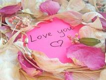 Kocha ciebie wiadomo?? na r??owej kleistej notatce z suchymi kwiat?w p?atkami, bi?uteria ?a?cuchem na drewnianym tle i pier?cionk zdjęcia royalty free