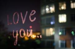 Kocha ciebie, wpisowy tekst pomadką na nadokiennym szkle w nocy pocałunek miłości człowieka koncepcja kobieta Fotografia Stock