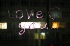 Kocha ciebie, wpisowy tekst pomadką na nadokiennym szkle w nocy pocałunek miłości człowieka koncepcja kobieta Obrazy Stock