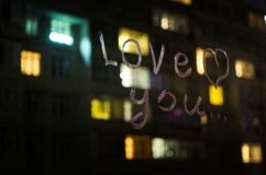 Kocha ciebie, wpisowy tekst pomadką na nadokiennym szkle w nocy pocałunek miłości człowieka koncepcja kobieta Zdjęcia Stock