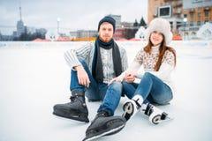 Kocha pary w łyżwach siedzi na lodzie, łyżwiarski lodowisko fotografia stock