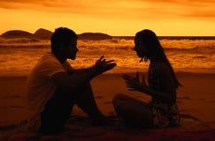 Kocha pary z związek szykanami przy plażą przy zmierzchem zdjęcie stock