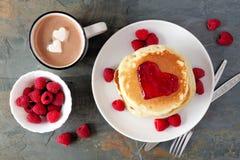 Kocha pojęcie śniadaniowych bliny, gorącą czekoladę i malinki nad łupkiem, fotografia stock