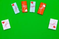 Kocha prezentów pudełka na zielonym tle z sercami Zdjęcie Stock