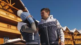 Kochająca para na tle drewniana chałupa w górach przy ośrodkiem narciarskim zbiory wideo