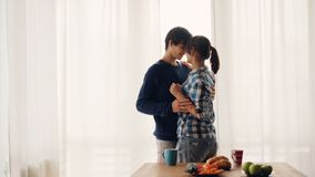 Kochający młodzi ludzie męża i żona tanczą w kuchni, całować i ono uśmiecha się roześmianych cieszący się romantycznego moment pr zbiory wideo