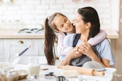 Kochaj?ca c?rka ?ciska jej matki na kuchni obrazy royalty free