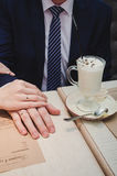 Kochająca kobieta chwyta mężczyzna ręka Właśnie para małżeńska pokazuje up obrączki ślubne Blisko filiżanki latte kawa z czekolad obrazy stock