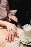 Kochająca kobieta chwyta mężczyzna ręka w ona ręki Właśnie para małżeńska pokazuje up obrączki ślubne Blisko filiżanki latte kawa obrazy royalty free