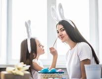 Kochająca matka, jej córka i each inny biel maluje Easter jajka zabawę Wygodna domowa atmosfera Wielkanoc obrazy royalty free