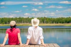 Kochająca para cieszy się pięknego jeziornego obsiadanie na drewnianym pi Obrazy Stock