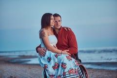Kochająca para, kobieta siedzi na jej męża ` s podołku, odpoczywa na plaży przeciw tłu jaskrawy świt obraz royalty free