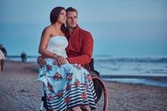 Kochająca para, kobieta siedzi na jej męża ` s podołku, odpoczywa na plaży przeciw tłu jaskrawy świt zdjęcia royalty free