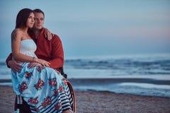 Kochająca para, kobieta siedzi na jej męża ` s podołku, odpoczywa na plaży przeciw tłu jaskrawy świt zdjęcie stock