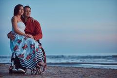 Kochająca para, kobieta siedzi na jej męża ` s podołku, odpoczywa na plaży przeciw tłu jaskrawy świt obrazy stock