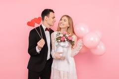 Kochająca para, mężczyzna trzyma dwa papierowego serca i kobiety trzyma bukiet, kwiaty i balony, na różowym tle zdjęcia stock