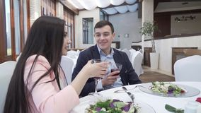 Kochająca para pije czerwone wino przy gościa restauracji zapasu materiału filmowego wideo w restauraci zbiory