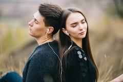 Kochająca para słucha muzykę wpólnie plenerową w jesieni zdjęcia stock