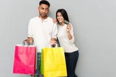 Kochająca para stoi nad popielatą ścianą i trzyma torba na zakupy Obrazy Stock