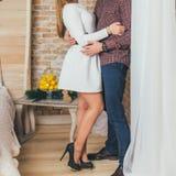 Kochająca para stoi przy okno i mężczyzna uściśnięciami kobieta obrazy stock
