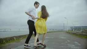 Kochająca para tanczy wpólnie na brzeg rzeki Kobieta w ładnej kolor żółty sukni zdjęcie wideo