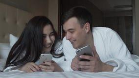 Kochająca para w białych żakietach na łóżka szczęśliwie części informaci w ich iPhones zwolnionego tempa zapasu materiału filmowe zbiory wideo