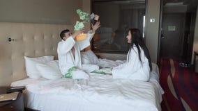 Kochająca para w białych żakietach na łóżku joyfully rzuca up gotówkowego, dużego wygrania zwolnionego tempa zapasu materiału fil zdjęcie wideo