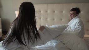 Kochająca para w białych żakietach na łóżku szczęśliwie walczy z poduszki zwolnionego tempa zapasu materiału filmowego wideo zdjęcie wideo