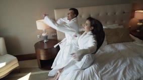 Kochająca para w białych żakietach szczęśliwie skacze na łóżkowym zwolnione tempo zapasu materiału filmowego wideo zbiory