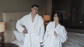 Kochająca para w białych żakietach szczęśliwie skacze na łóżkowym zwolnione tempo zapasu materiału filmowego wideo zdjęcie wideo
