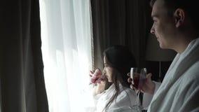 Kochająca para w bielu pokrywa spojrzenia przy krajobrazowym na zewnątrz okno facet przynosi dziewczynie szkło czerwone wino zapa zbiory wideo