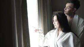 Kochająca para w bielu pokrywa spojrzenia przy krajobrazowym outside okno i buziaki zaopatrują materiału filmowego wideo zbiory wideo