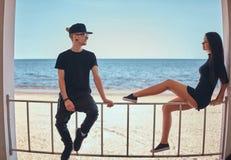 Kochająca para w eleganckich ubraniach siedzi na poręczu i patrzeje each inny przeciw pięknemu dennemu wybrzeżu obrazy stock