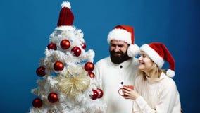 Kochająca para z szczęśliwymi twarzami spotyka nowego roku blisko choinki Potomstwa dobierają się w nowy rok kapeluszach dekorują zbiory