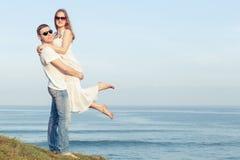 Kochająca pary pozycja na plaży przy dnia czasem zdjęcia stock