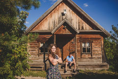Kochająca romantyczna para w wiosce blisko drewnianego domu, Mężczyzna siedzi na ganeczku, młoda kobieta w przedpolu Zdjęcie Royalty Free