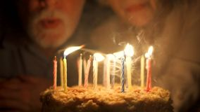 Kochająca starsza pary odświętności rocznica z tortem w wieczór w domu podmuchowe świeczki zdjęcie wideo