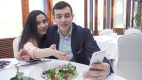 Kochająca szczęśliwa para w restauraci kłaść niedorzecznego selfie w instagram przez iPhone zwolnionego tempa zapasu materiału fi zbiory wideo