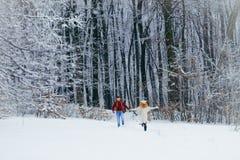 Kochająca uśmiechnięta para ma zabawę podczas gdy biegający wzdłuż śnieżnego lasowego Długiego widoku Święta tła blisko czerwony  Obraz Stock