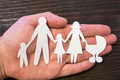 Kochające rodzinne mienie ręki Papier postacie na tle mahoń Obraz Stock