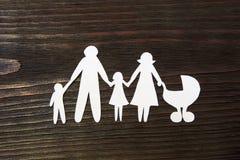 Kochające rodzinne mienie ręki Papier postacie na tle mahoń Zdjęcie Stock