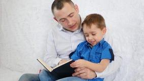 Kochającego rodzica mężczyzna czyta ciekawą książkę jego ciekawy mały syn na białej kanapie w domu