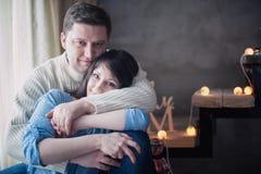 Kochającej pary siedzący obejmowanie na schody dekorował z Bożenarodzeniową girlandą obrazy royalty free