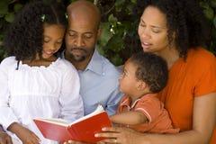 Kochający amerykanin afrykańskiego pochodzenia wychowywa czytanie z ich dzieciakami Zdjęcia Royalty Free
