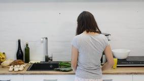 Kochający facet ściska jego uśmiechniętej dziewczyny w ich kuchni w ranku z śniadaniem robi w zwolnionym tempie wcześnie zbiory