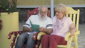 Kochający mąż czyta książce pięknej żony, starzy ludzie relaksuje w kołysać krzesła zbiory
