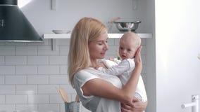 Kochający matka chwyty na rękach nowonarodzona dziewczynka, portret młodej kobiety delikatnie całować jej dziecka przy kuchnią i  zbiory wideo