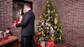 Kochający para taniec przy przyjęciem, mężczyzna przytulenia kobieta, nowego roku ` s przyjęcie blisko choinki rodzina jest piękn zbiory wideo